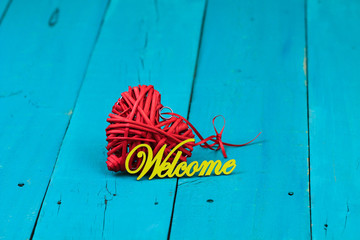 Welcome sign with red wicker heart on wood background