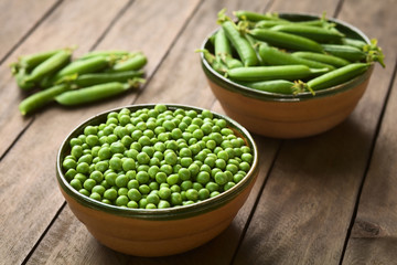 Peas (lat. Pisum sativum) and closed peapods in bowls (Selective Focus, Focus into the middle of the peas)