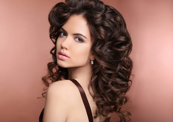 Healthy hair. Makeup. Beautiful brunette girl with long curly ha
