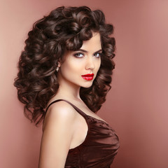 Curly hairstyle. Beautiful smiling woman with red lips makeup an
