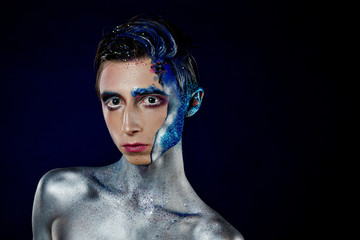 Crazy young androgyne man with face art. SPACEMAN. Freak person. Tinsel creative blue makeup. Intersex and anorexia concept. Space for logo