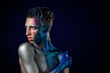 Crazy young androgyne man with face art. SPACEMAN. Freak person. Tinsel creative blue makeup. Intersex and anorexia concept. Space for logo. HOMOSEXUALITY