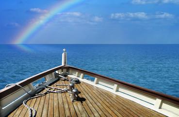 Ship in a calm sea. Rainbow on the horizon.