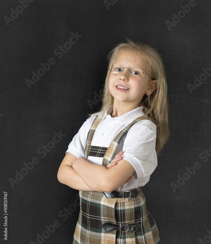 114305da4 sweet junior schoolgirl with blonde hair standing and smiling happy isolated  in blackboard background