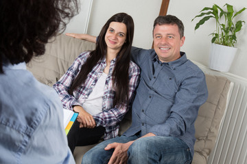 Married couple is visiting, psychologist, on the sofa and talking.