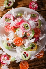 Several fruit candies with fruit motifs in white bowl