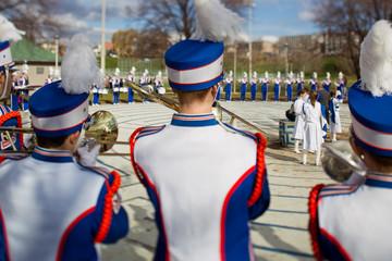rear view of men wearing fur hat playing trumpet.
