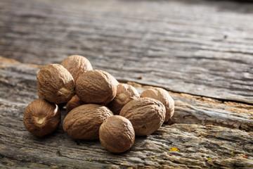 Fototapeta Dried nutmeg seeds set on old wooden surface obraz