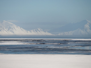 Snowy calm landscape. Blue ocean and white mountains