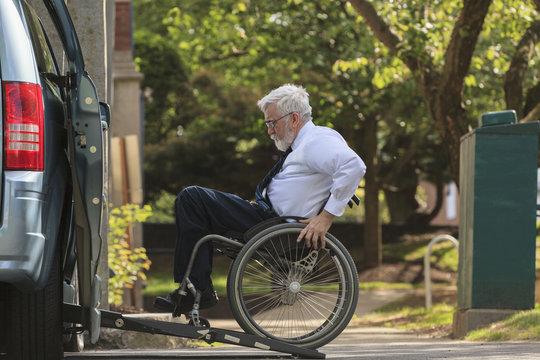 Caucasian businessman in wheelchair entering van