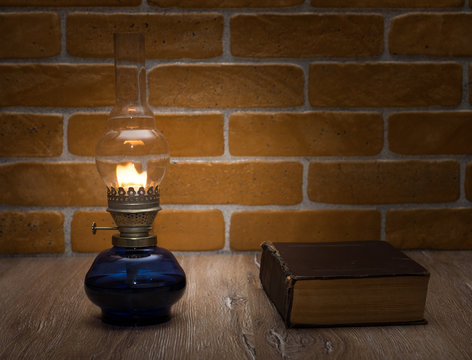The book by the light of an old lamp. Glass oil lamp and book on the wooden table against the background of a brick wall.