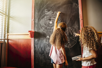 Mixed race sisters drawing on chalkboard