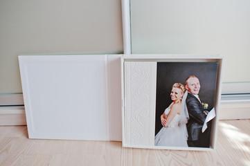 White leather wedding album with photo on canvas of newlyweds