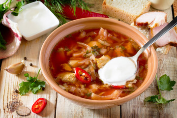 Vegetable soup with beetroot (borscht) on a wooden table, the na