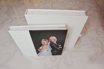 White leather wedding album with photo on canvas of newlyweds