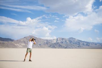 Hispanic man photographing in remote desert