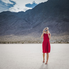 Hispanic woman photographing in remote desert