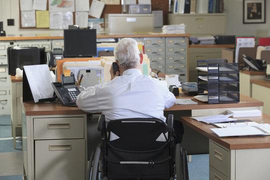 Caucasian businessman talking on phone in office