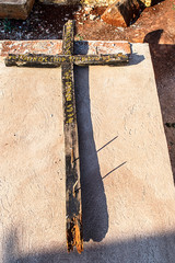 Old wooden cross lying on a grave
