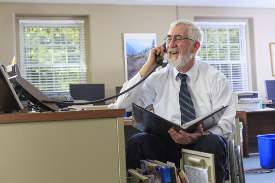 Caucasian businessman talking on phone at desk