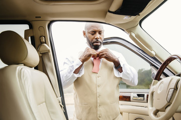 Black man tying bow tie in car