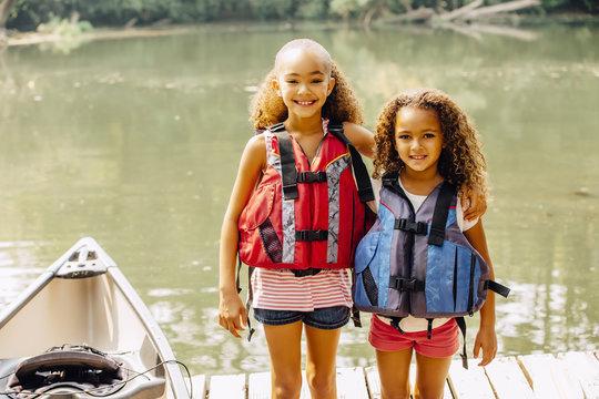 Mixed race sisters wearing life jackets at lake