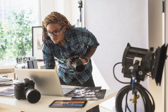 Mixed race photographer using laptop in studio