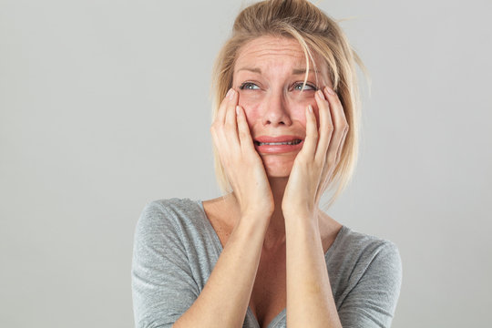 drama concept - crying young blond woman in pain with big tears expressing her disappointment and sadness, grey background studio.
