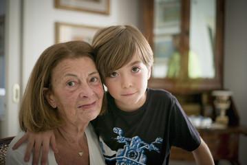 Caucasian grandmother and grandson hugging