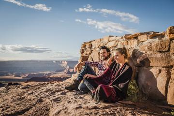 Hispanic couple sitting on remote hilltop