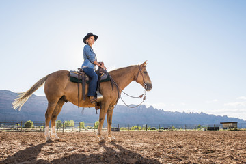 Hispanic woman riding horse on ranch