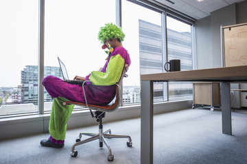 Caucasian businessman wearing clown costume in office