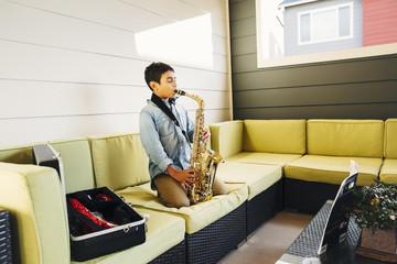 Mixed race boy playing saxophone on sofa