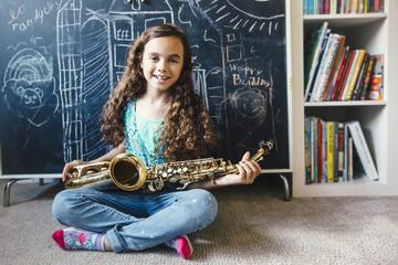 Mixed race girl holding saxophone on floor