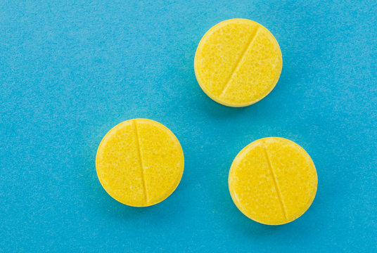 yellow tablets pills on a blue background