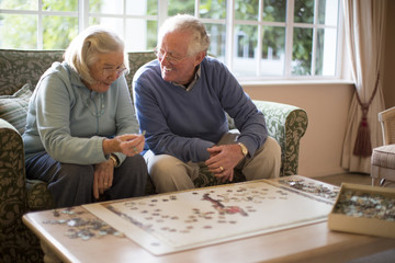 Older couple on sofa solving jigsaw puzzle