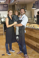 Caucasian family business owners smiling in cafe