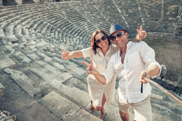 Couple in love take a selfie photo in ancient amphitheater in th