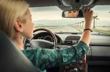 Woman in car look in rear view mirror