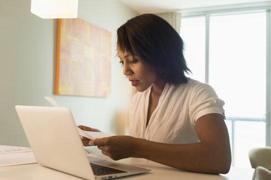 African American woman paying bills on laptop