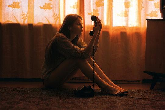 Caucasian woman sitting on floor staring at telephone
