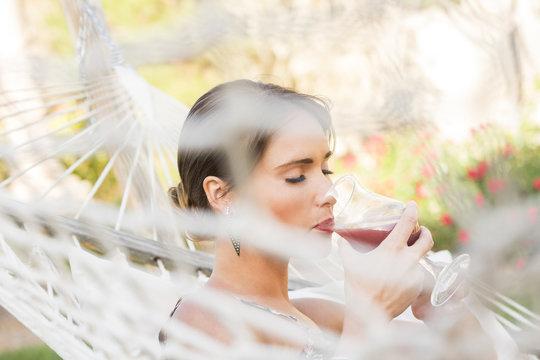 Caucasian woman drinking cocktail in hammock