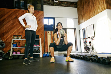 Woman working out with trainer in gymnasium