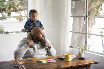African American father holding baby son on shoulders