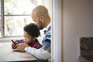 Mixed race father and son using cell phone at table