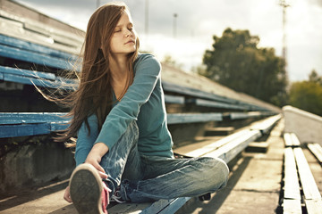 Caucasian woman sitting on bleachers