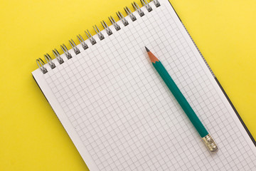 notebook and pencil on a yellow background