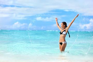 Wall Mural - Happy bikini woman having fun swimming in ocean. Freedom bikini woman carefree with arms up splashing water in joy on tropical beach. Success Asian girl on summer Caribbean travel vacation.