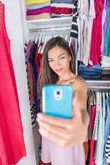 Asian girl taking a smartphone selfie of her fashion outfit in bedroom closet. Woman using styling app on phone to take a photo of her new clothing at home or store fitting room. Shopping concept.