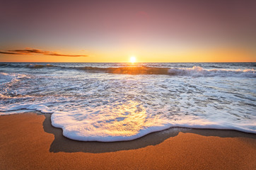 Colorful ocean beach sunrise with deep blue sky and sun rays.
